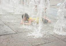 Una muchacha asiática que juega por la fuente de agua Foto de archivo