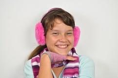Una muchacha astuta con los manguitos del oído y los guantes cortados Fotos de archivo libres de regalías