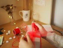 Una muchacha ata una cinta de Tulle en un regalo, preparando una sorpresa imagenes de archivo