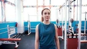 Una muchacha atlética joven camina a través de un gimnasio vacío almacen de metraje de vídeo