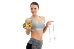 Una muchacha atlética joven en top sostiene una placa de la ensalada y de una cinta métrica Imagen de archivo libre de regalías