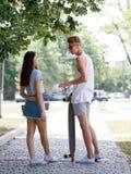 Una muchacha atractiva al lado de su novio lindo con un longboard en un fondo borroso del parque Relación y amor Imagen de archivo libre de regalías