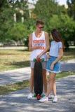 Una muchacha atractiva al lado de su novio lindo con un longboard en un fondo borroso del parque Relación y concepto del amor Foto de archivo