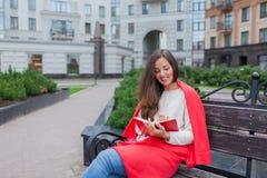 Una muchacha atractiva con el pelo marrón largo y una sonrisa blanca del diente se sienta en un banco y le escribe pensamientos e Fotos de archivo