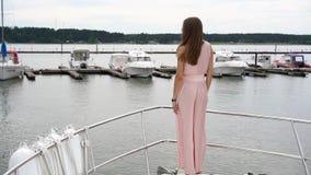 Una muchacha atractiva en un vestido se coloca en un barco en el fondo de otros barcos en el embarcadero y da vuelta metrajes