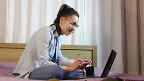 Una muchacha atractiva joven está escribiendo un mensaje en su ordenador portátil, sentándose en la cama en casa metrajes