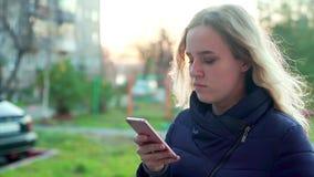 Una muchacha atractiva joven se está colocando en la calle con un smartphone en su mano metrajes
