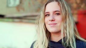 Una muchacha atractiva joven se está colocando en la calle, ella está sonriendo almacen de metraje de vídeo