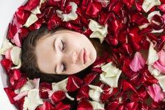 Una muchacha atractiva joven toma un cuarto de ba?o con los p?talos de la flor y se relaja contra la perspectiva de una luz hermo fotografía de archivo