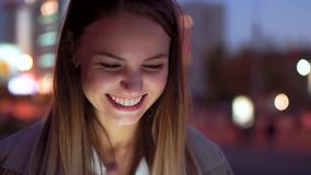 Una muchacha atractiva mira la tableta y las risas, contra el camino de la noche El movimiento lento, el resplandor de las luces metrajes