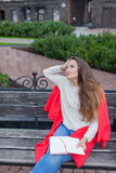 Una muchacha atractiva se sienta en un banco y le escribe pensamientos en el fondo urbano en un cuaderno rojo Ella lleva un suéte Fotografía de archivo