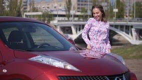 Una muchacha baila delante de un nuevo coche, miente en el parabrisas y abraza el coche 4K MES lento almacen de video
