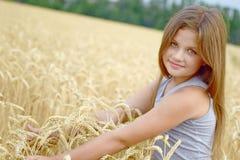 Una muchacha bastante feliz que abraza por las manos los oídos de oro del centeno en campo Concepto de pureza, crecimiento, felic Fotos de archivo libres de regalías