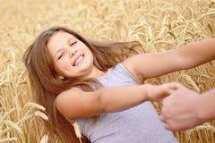 Una muchacha bastante feliz que ríe llevando a cabo las manos del ` s de la madre en centeno de oro coloca Concepto de pureza, cr Fotos de archivo libres de regalías