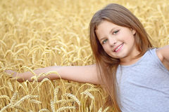 Una muchacha bastante feliz que toca a mano los oídos de oro del centeno en campo Concepto de pureza, crecimiento, felicidad Foto de archivo libre de regalías