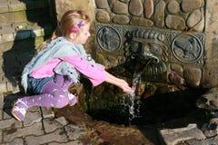Una muchacha bebe el agua a partir del resorte, Fotos de archivo libres de regalías