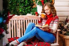 Una muchacha bebe té y lee un libro, sentándose en un banco la víspera del Año Nuevo ` S Eve del Año Nuevo Navidad Imagen de archivo