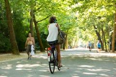 Una muchacha biking y que llama en un parque en Amsterdam Imágenes de archivo libres de regalías