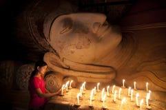 Una muchacha birmana hermosa para pagar su respecto a la estatua de Buda Foto de archivo