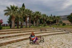 Una muchacha blanca en un vestido del hippie se sienta y descansa sobre un banco en el parque nacional de Pamukkale fotos de archivo