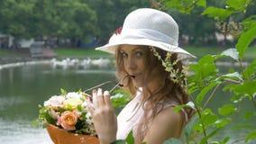 Una muchacha blanca hermosa en un sombrero blanco, con un ramo de flores almacen de video