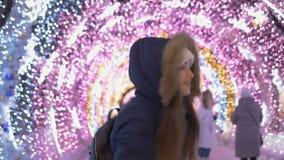 Una muchacha blanca hermosa es muy feliz Contra la perspectiva de la iluminación festiva almacen de metraje de vídeo