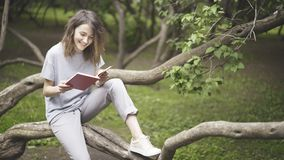 Una muchacha blanca morena de risa está leyendo un libro en el parque Imagenes de archivo