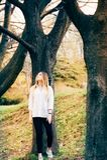 Una muchacha bonita en un parque con los árboles grandes foto de archivo