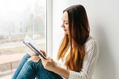 Una muchacha bonita está leyendo un libro que se sienta en la ventana Obtención del conocimiento, preparándose para los exámenes, Imagen de archivo