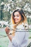 Una muchacha bonita goza de los árboles florecientes de la magnolia, su pelo largo en m imagenes de archivo