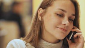 Una muchacha bonita joven lee y escribe mensajes en el teléfono que se sienta en un café en la tabla Primer Fotos de archivo libres de regalías