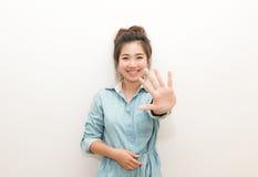 Una muchacha bonita que sonríe y que presenta los fingeres de la mano cinco Foto de archivo