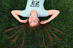 Una muchacha brillante joven ama deportes adolescente que miente en la opinión superior de la hierba Imagenes de archivo