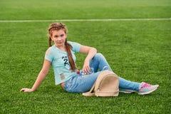 Una muchacha brillante joven ama deportes muchacha del adolescente que se sienta en el campo de la escuela Imagen de archivo