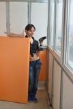 Una muchacha calienta la pared en el balcón Foto de archivo libre de regalías