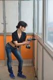 Una muchacha calienta la pared en el balcón Imágenes de archivo libres de regalías
