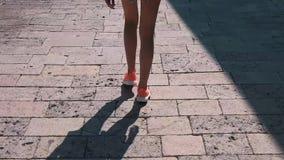 Una muchacha camina abajo de la calle con las piedras de pavimentación almacen de metraje de vídeo