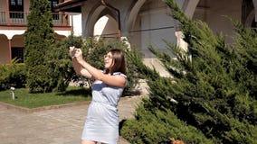 Una muchacha camina alrededor de las vistas de una ciudad desconocida excursión Jardín metrajes
