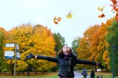 Una muchacha camina en el parque del otoño, lanzando follaje en el cielo Imágenes de archivo libres de regalías