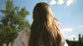 Una muchacha camina a lo largo de una calle de la ciudad con los auriculares y escucha la música contra el cielo azul excursión d metrajes