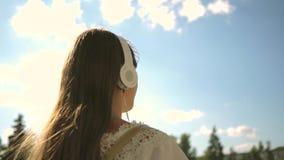Una muchacha camina a lo largo de una calle de la ciudad con los auriculares y escucha la m?sica contra el cielo azul C?mara lent almacen de metraje de vídeo