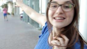 Una muchacha camina a través de la ciudad situada en la playa que sonríe y que presenta para la cámara almacen de metraje de vídeo