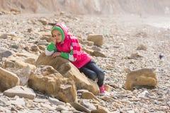 Una muchacha cansada aburrida coloca en una roca grande por el mar Foto de archivo libre de regalías
