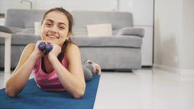 Una muchacha cansada miente en el piso y las sonrisas almacen de metraje de vídeo