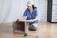 Una muchacha caucásica monta los nuevos muebles mientras que se sienta en piso fotos de archivo