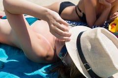 Una muchacha cerrada-para arriba en un sombrero en una playa con un amigo Fotos de archivo