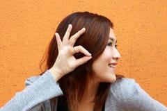 Una muchacha china que está oyendo la voz Fotografía de archivo