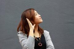 Una muchacha china que está oyendo la voz Imagen de archivo libre de regalías