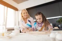 Una muchacha con una abuela que desarrolla una pasta para una empanada hecha en casa Tienen delantales de la cocina Fotos de archivo libres de regalías