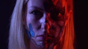Una muchacha con bodypainting de mariposas azules en su cara mira a su amigo con el odio, cámara lenta almacen de metraje de vídeo